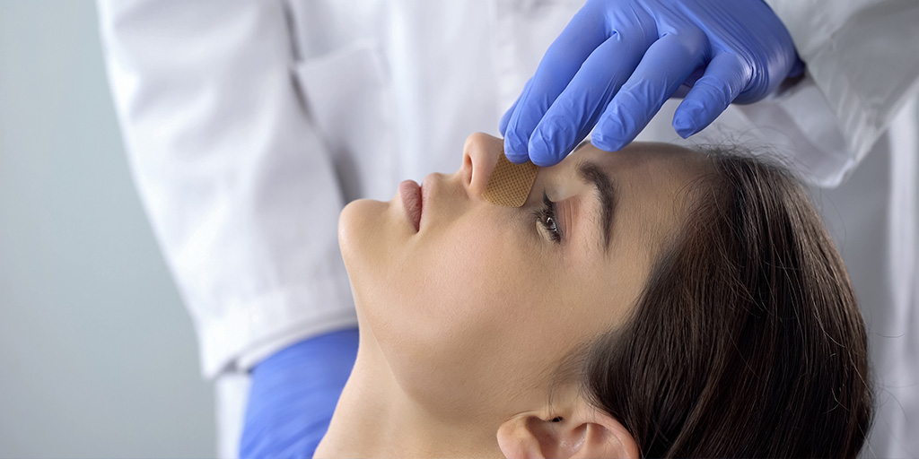 Doctor checking woman's nose