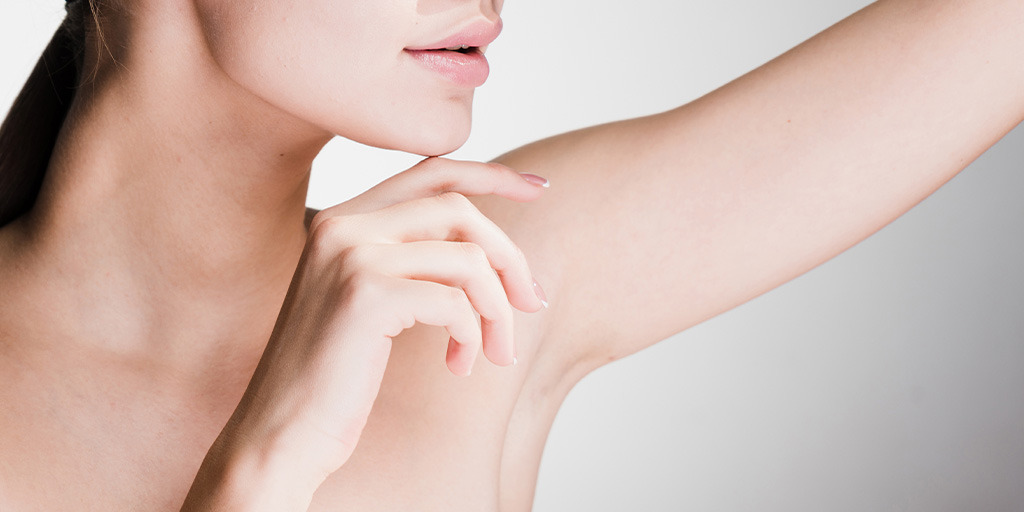 Woman looking at her underarm area